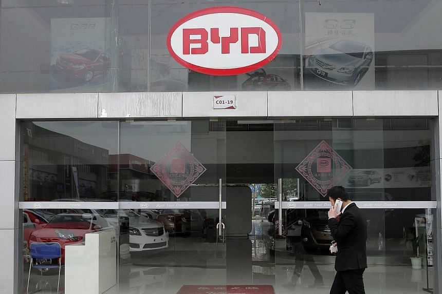 A man walks past a BYD store in Wuhan, Hubei province, March 20, 2014. Shares of Chinese carmaker BYD Co fell 5 per cent in Hong Kong after the company launched a new share issue seeking to raise up to US$551 million (S$690 million). -- FILE PHOTO: R