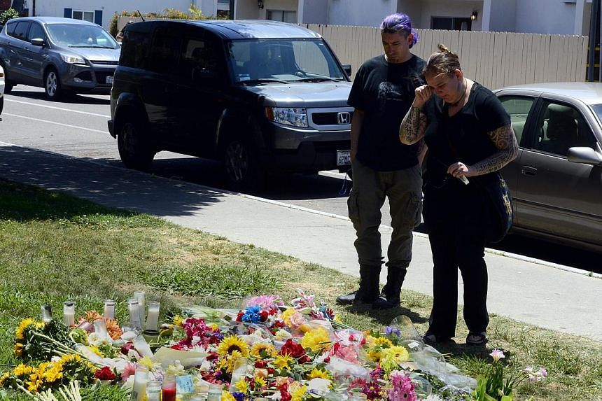 A woman cries as she looks at a make-shift memorial set up outside the Alpha Phi sorority where two women died during the deadly shooting rampage at the college town of Isla Vista, California, USA, May 25, 2014. -- PHOTO: EPA