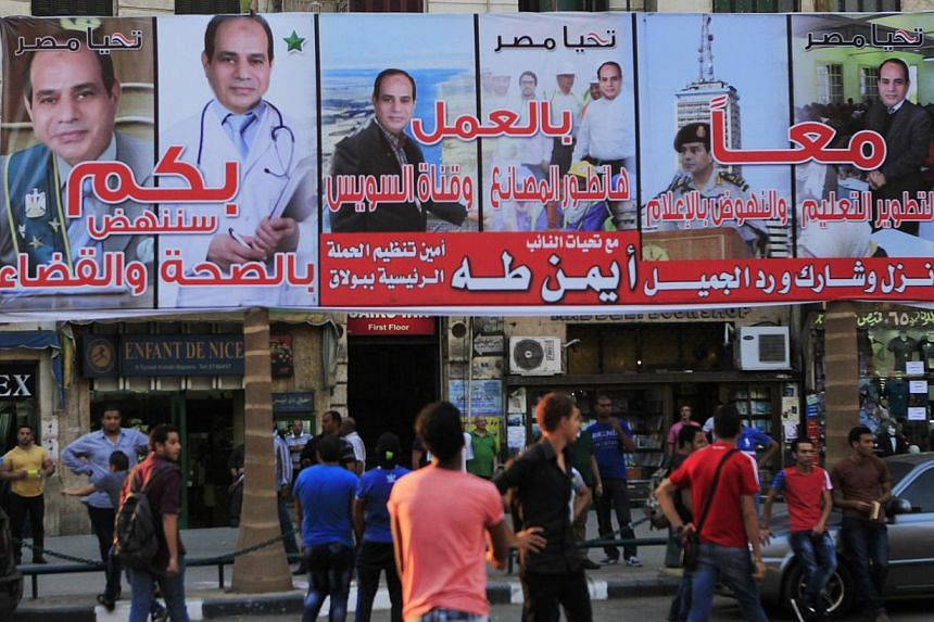 People walk under an election campaign billboard of presidential candidate and former army chief Abdel Fattah al-Sisi a day ahead of presidential elections at Talaat Harab Square in Cairo May 25, 2014. -- PHOTO: REUTERS