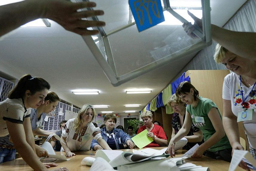 Members of the election commission empty ballot boxes in a polling station in Kiev on May 25, 2014. -- PHOTO: REUTERS