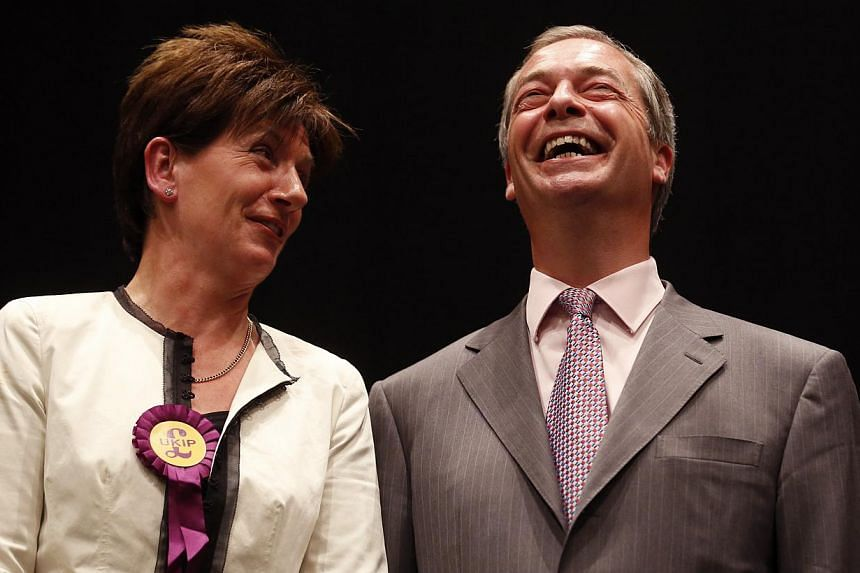UK Independence Party (UKIP) leader Nigel Farage and UKIP candidate Diane Jones (left) smile after the declaration of results of the European Parliament election for the south east region, in Southampton, southern England May 25, 2014. -- PHOTO: REUT