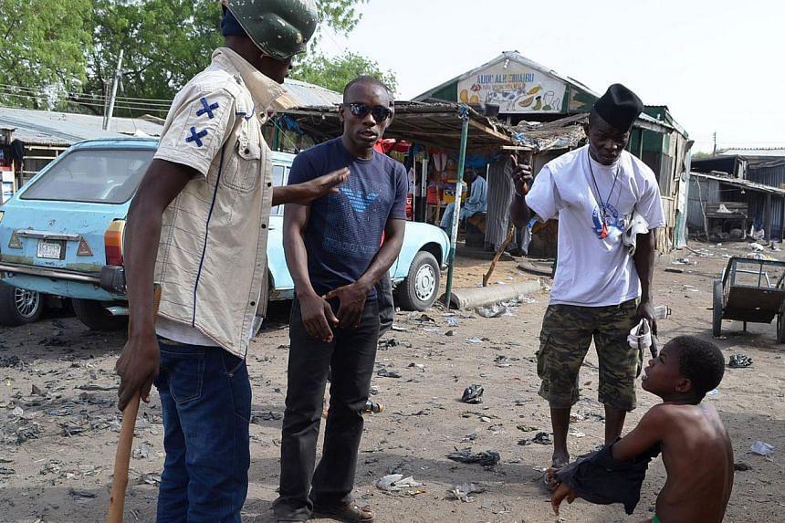 Vigilantes dubbed 'Civilian JTF' interrogate a suspected Boko Haram informant in Jajeri neighbourhood of the north-east Nigerian city of Maiduguri on May 24, 2014. -- PHOTO: AFP