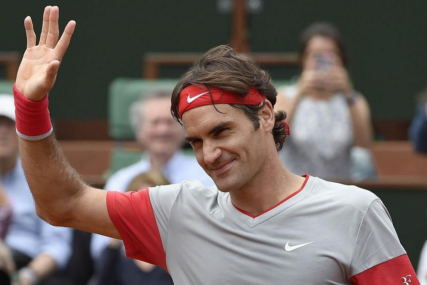 Switzerland's Roger Federer waves at the crowd after winning his French tennis Open first round match at the Roland Garros stadium in Paris on May 25, 2014. -- PHOTO: AFP