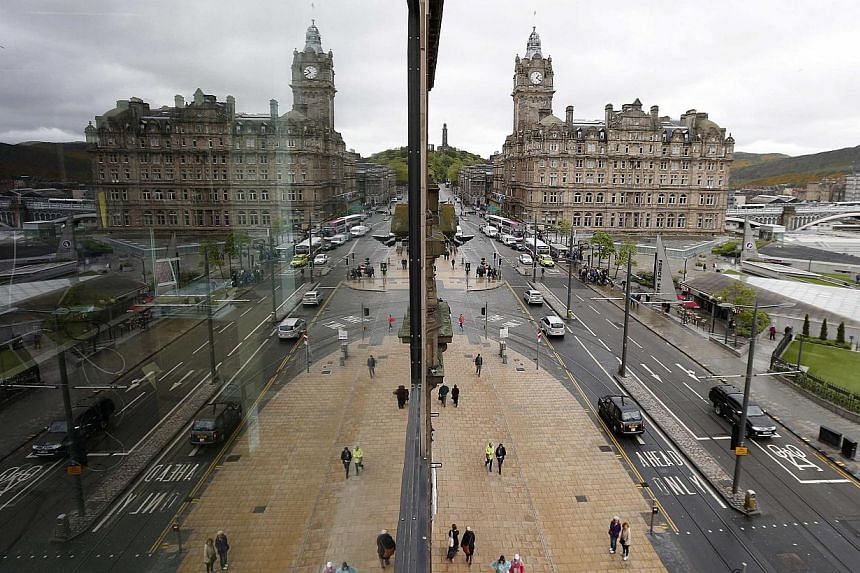 Pedestrians walk along Princes Street, the main shopping street in Edinburgh, Scotland May 1, 2014. Britain's finance ministry stepped up its attack on the Scottish government's independence plans on Monday, saying it had not fully budgeted for s
