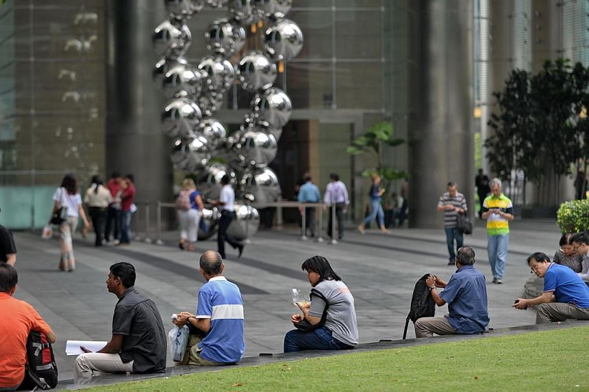 People sit along the walkway at Raffles place financial district in Singapore on April 30, 2014. Most Singaporeans do not think they will be able to retire at their desired age, according to a new survey by insurer Aviva. -- FILE PHOTO: AFP
