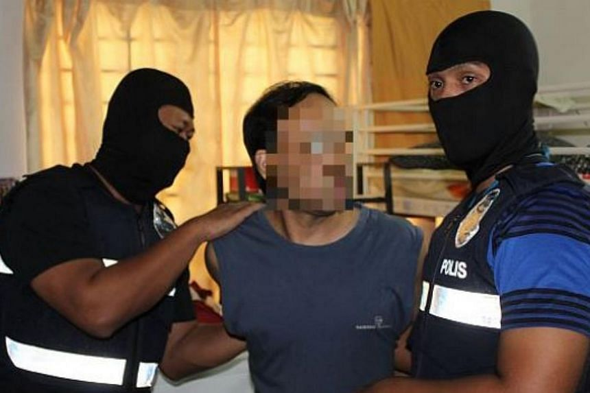 One of the three Sri Lankan men being detained by police officers in Bandar Utama. -- PHOTO: THE STAR/ASIA NEWS NETWORK