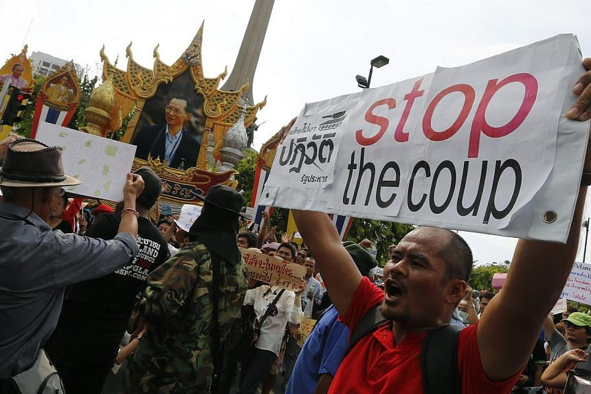 A Thai anti-coup protester holds a placard and shout slogans during a protest against coup at Victory Monument in Bangkok, Thailand, May 25, 2014. -- PHOTO: EPA