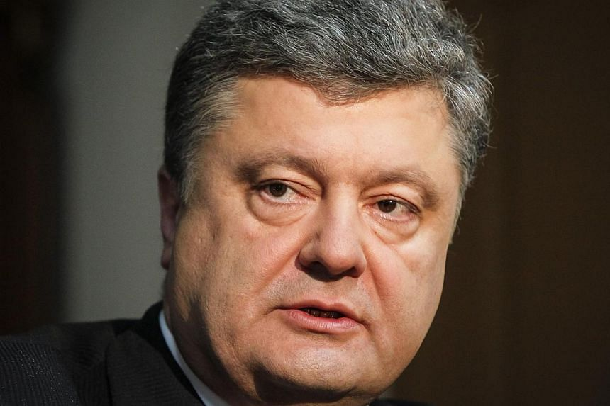 Petro Poroshenko listens during an interview with Reuters in Kiev in this April 4, 2014 file photo. -- FILE PHOTO: REUTERS