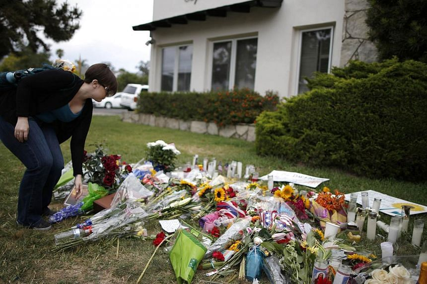 A University of California, Santa Barbara graduate student lays flowers at a makeshift memorial in front of the Alpha Phi sorority house where two women were killed. Police in the California community where a man killed six college students said they