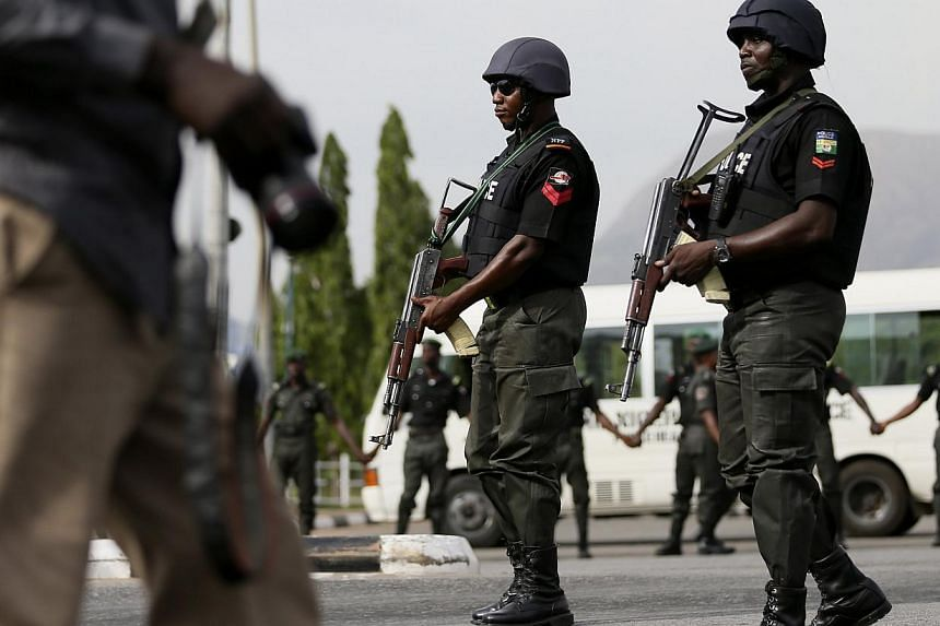 """Police officers patrol near a journalist during a protest by the Abuja wing of the """"Bring Back Our Girls"""" group, calling for the release of the Nigerian schoolgirls in Chibok who were kidnapped by Islamist militant group Boko Haram, in Abuja on May 2"""