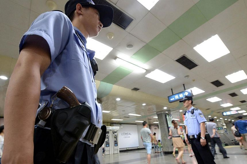 """Armed policemen stand guard in a subway in Beijing on May 23, 2014. Chinese police have broken up a """"terrorist gang"""" in the restive western region of Xinjiang, the local government said on Tuesday. -- PHOTO: AFP"""