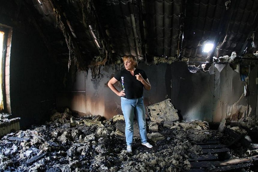 A woman looks at her building destroyed as a result of Monday's combat of Ukrainian troops with pro-Russia separatists near the International airport in Donetsk on May 27, 2014.Ukrainian forces fought with separatists in the city of Donetsk for
