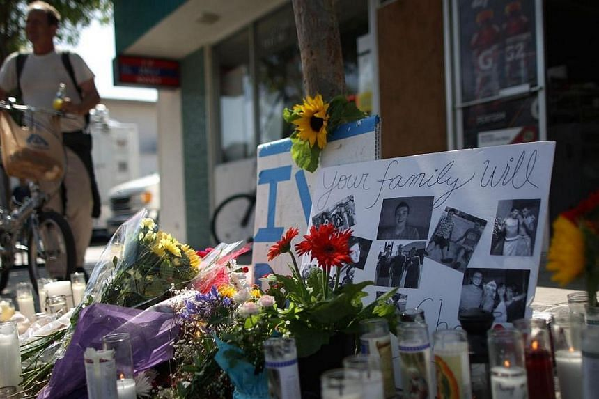 Photos of a victim stand in a makeshift memorial in front of the IV Deli on May 25, 2014 in Isla Vista, California. Penang-born Ong Li Chin raced against time in a desperate bid to save her son Elliot Rodger from making a fatal mistake. -- PHOTO