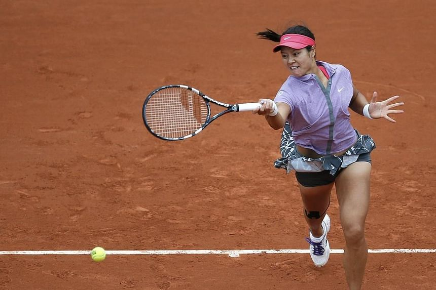 Li Na of China returns a forehand to Kristina Mladenovic of France during their women's singles match at the French Open tennis tournament at the Roland Garros stadium in Paris on May 27, 2014.Australian Open champion Li Na of China was knocked