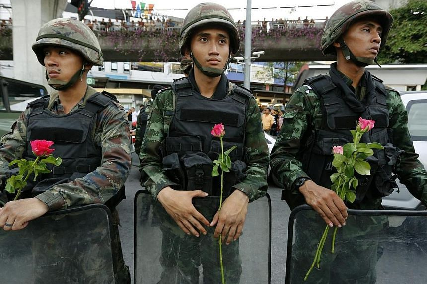 Thai armed soldiers hold flowers as they stand by as anti-coup protesters rally against the military junta at Victory Monument in Bangkok, Thailand on May 27, 2014.Thailand's ruling body, the National Council for Peace and Order, announced on T