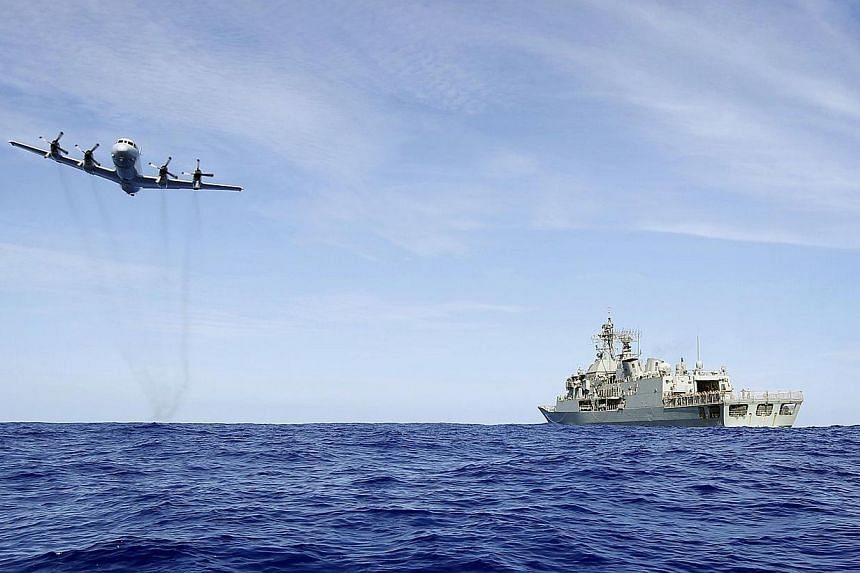 A photo taken on April 7, 2014 and released by Australian Defence on April 11 shows a Royal Australian Air Force AP-3C Orion from 92 Wing, conducting a low level fly by before dropping stores to HMAS Toowoomba during the search for the missing Malays