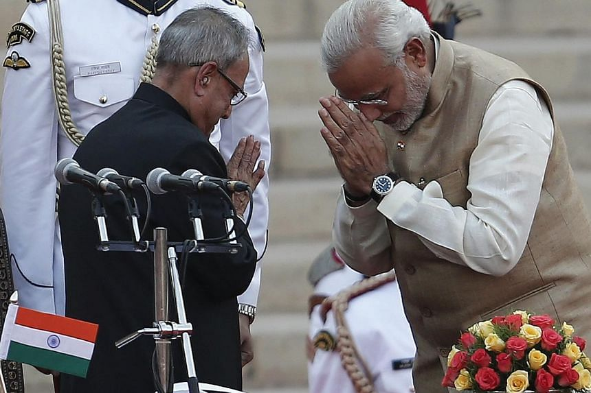 India's Prime Minister Narendra Modi (right) greets India's President Pranab Mukherjee after taking his oath at the presidential palace in New Delhi on May 26, 2014. -- PHOTO: REUTERS