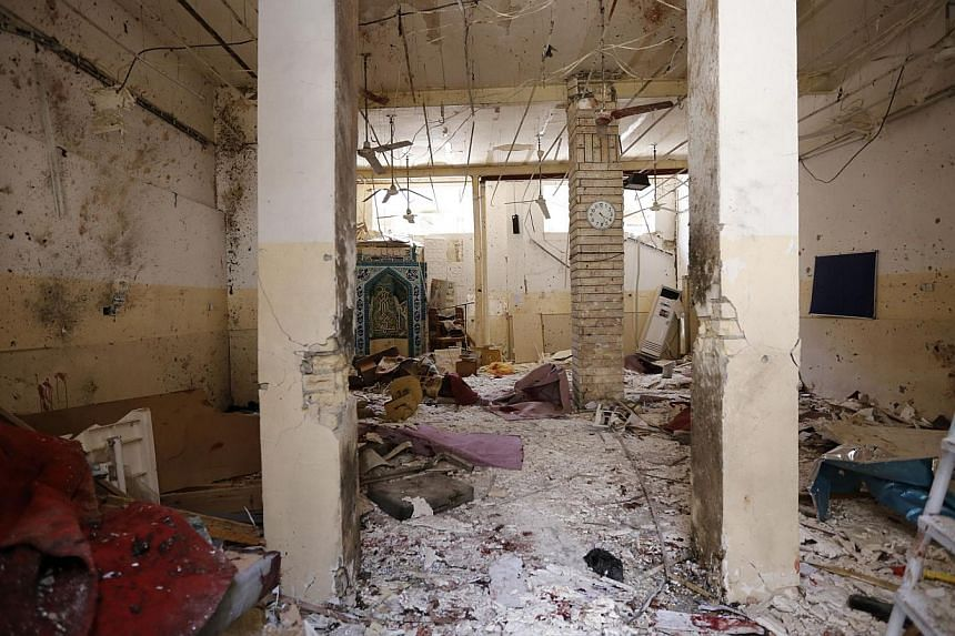 Debris lies strewn at the site of a bomb attack inside a Shi'ite mosque in Baghdad on May 27, 2014.A suicide bomber blew himself up inside a Shi'ite mosque in central Baghdad on Tuesday, killing at least 19 people, security and medical sources
