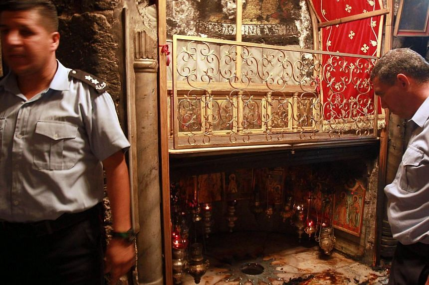 Palestinian police inspect the Grotto, at the Church of the Nativity, believed to be the birthplace of Jesus Christ, on May 27, 2014. A fire broke out just hours after Pope Francis wrapped up a three-day Middle East pilgrimage which saw him visit the