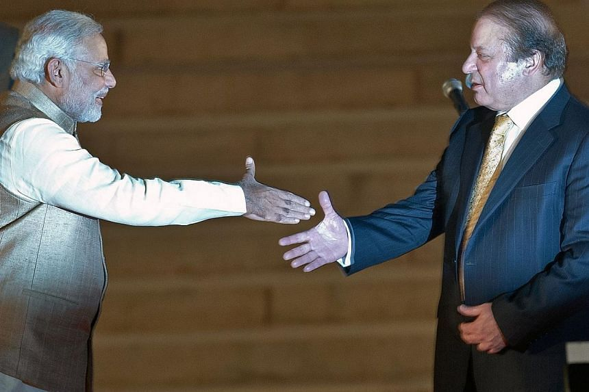 Newly sworn-in Indian Prime Minister Narendra Modi (left) prepares to shake hands with Pakistani Prime Minister Nawaz Sharif after the swearing-in ceremony at the Presidential Palace in New Delhi on May 26, 2014. -- PHOTO: AFP