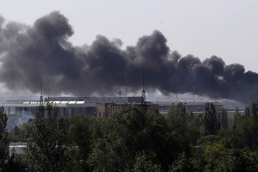 Smoke billows from Donetsk international airport during heavy fighting between Ukrainian and pro-Russian forces on May 26, 2014.European security watchdog OSCE said on Tuesday it had lost contact with one of its teams of monitors near the town