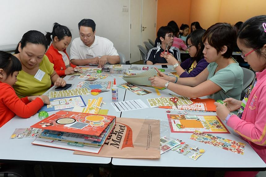 Children and their parents working on their stories at a scrapbooking workshop where they are guided by trainers from Papermarket. Every story-maker will receive a copy of STep: My Year In The News, as part of the camp.