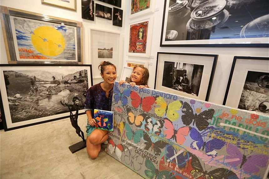 Netherlands artist Casper Faassen signs on the back of an artwork for a customer who has bought it; while Mrs Christina Thorsen (above) and her daughter Kayla show a painting they bought for $3,000. -- ST PHOTO: ONG WEE JIN