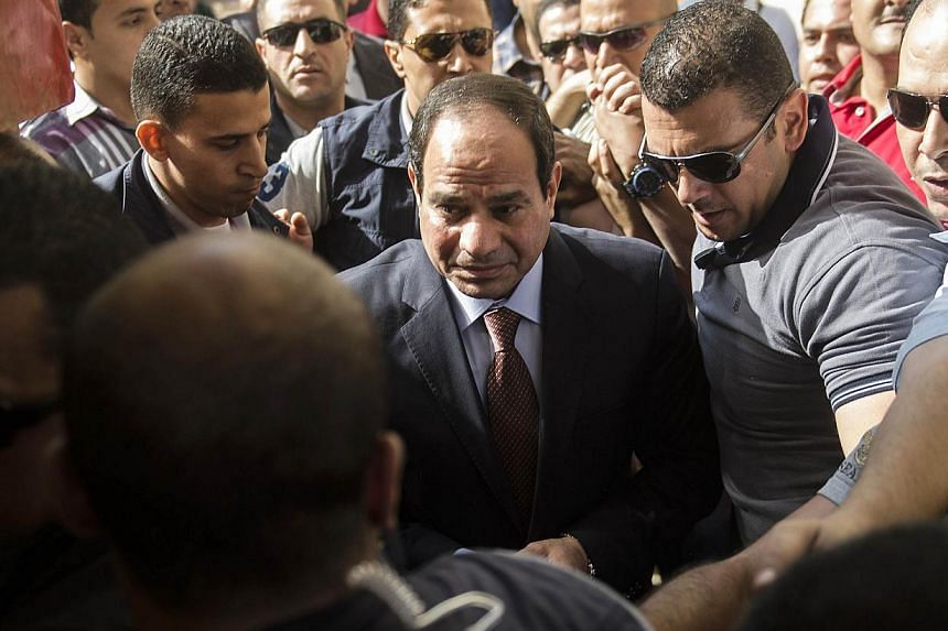 Egypt's former army chief and leading presidential candidate Abdel Fattah al-Sisi (centre) arriving at a polling station in Heliopolis, Cairo, yesterday to vote.
