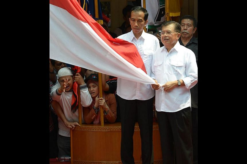Mr Joko (left) and his running mate Mr Kalla holding Indonesia's national flag during a declaration as presidential and vice-presidential candidates in Jakarta on Monday last week. The next vice-president will be a seasoned politician with much more