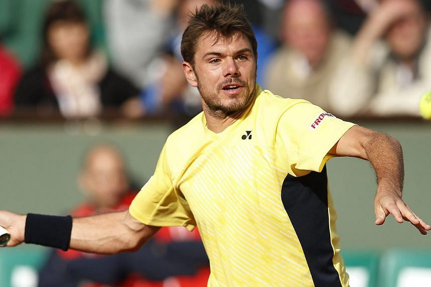Stan Wawrinka of Switzerland returns to Guillermo Garcia-Lopez of Spain during their first round match for the French Open tennis tournament at Roland Garros in Paris, France on May 26, 2014. -- PHOTO: EPA