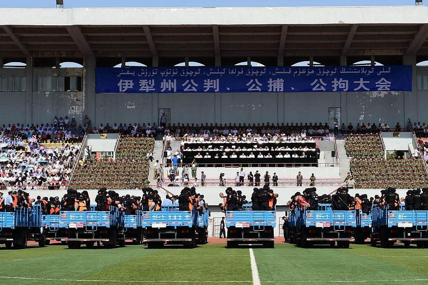 This picture taken on May 27, 2014 shows security forces standing behing the accused wearing orange vests on trucks during a mass sentencing in Ili prefecture, northwest China's Xinjiang region. Authorities in China's mainly Muslim Xinjiang mounted a