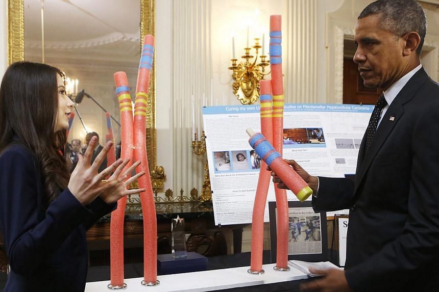 US President Barack Obama (right) looks at the Cancer Research project of Elena Simon (left), New York, NY, during the 2014 White House Science Fair at the White House, Washington DC, USA, on May 27, 2014. The Science Fair features winners of a broad