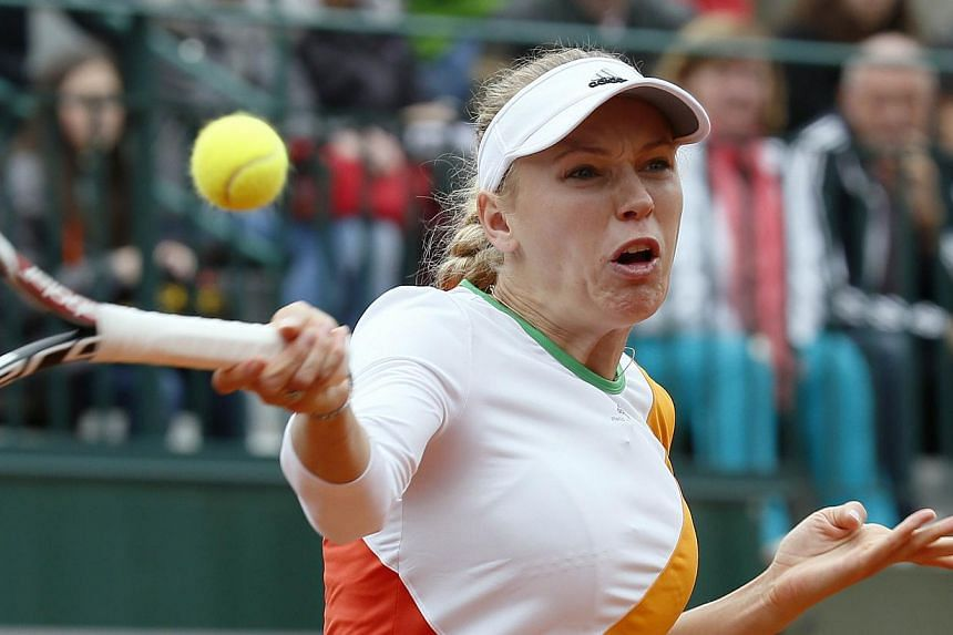 Denmark's Caroline Wozniacki returns the ball to Belgium's Yanina Wickmayer during their French tennis Open first round match at the Roland Garros stadium in Paris on May 27, 2014. -- PHOTO: AFP