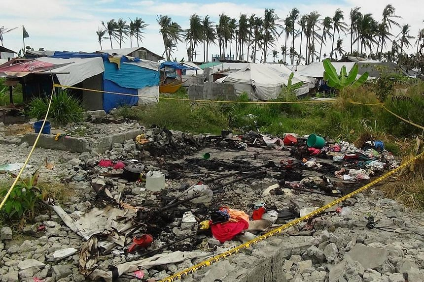 A police line is seen while remains of a tent serving as temporary shelter for victims of Super Typhoon Haiyan, was burned in San Jose village, Tacloban City Leyte province, central Philippines on May 28, 2014.Six members of the same family die