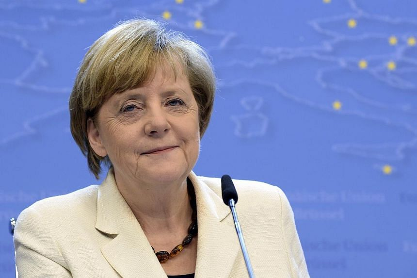 German Chancellor Angela Merkel talks to the media following an informal dinner of European Union heads of state or government at the EU Council in Brussels on May 27, 2014. Merkel topped Forbes's list of the world's most powerful women for the