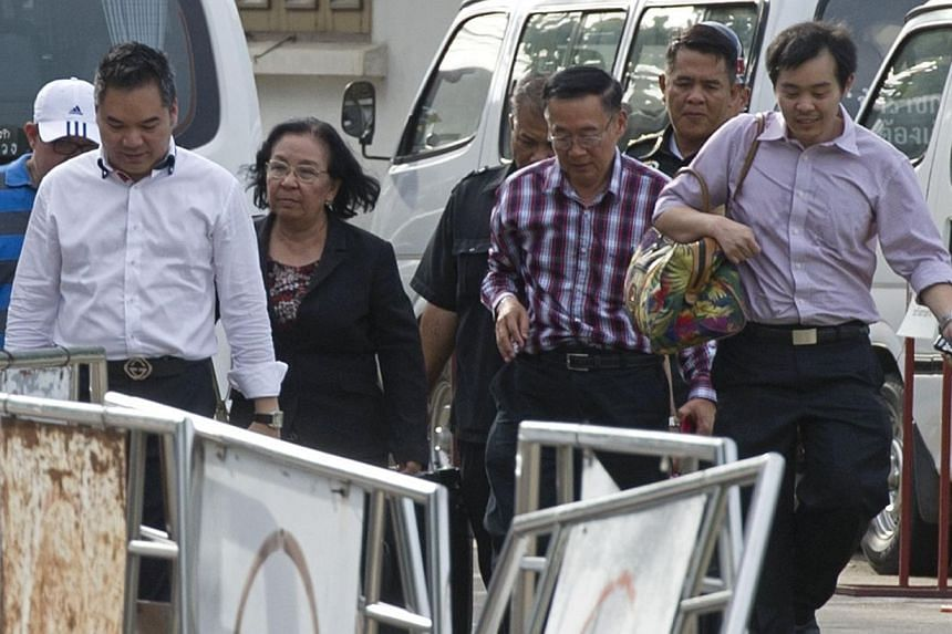 """""""Red Shirt"""" protest leaders Tida Tawornseth (2nd left) and her husband Weng Tojirakarn (2nd right) walk after being released from an army facility in Bangkok on May 28, 2014.Thailand's junta on Wednesday, May 28, 2014, freed leaders of the """"Red"""
