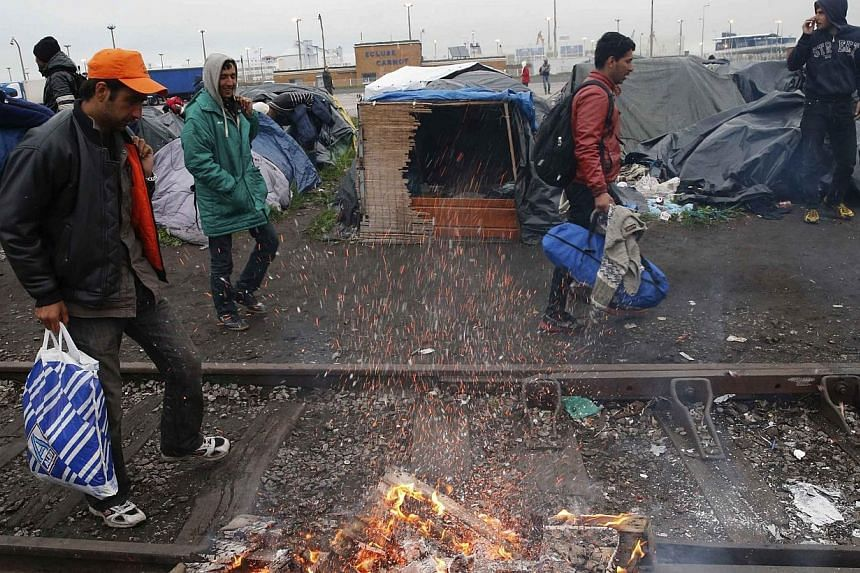 Immigrants leave their makeshift shelter as French police evacuate them from an improvised camp in Calais, northern France on May 28, 2014.French police on Wednesday, May 28, 2014, expelled around 550 people from makeshift camps in the northern