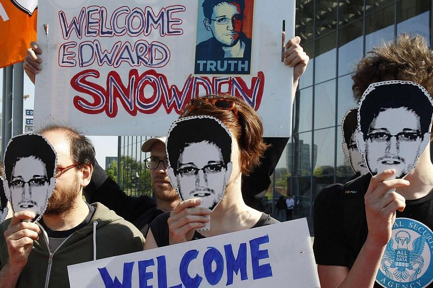 Protesters hold masks depicting former U.S. National Security Agency contractor Edward Snowden during a demonstration in Berlin on May 22, 2014. Secretary of State John Kerry on Wednesday, May 28, 2014, said fugitive intelligence leaker Edward S