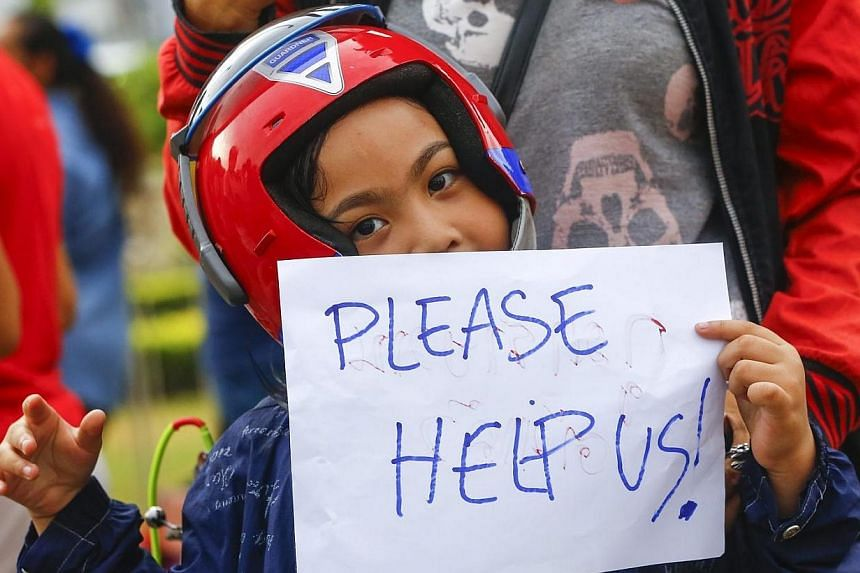 """A young boy holds a sign reading 'Please help us', during a protest against the military coup at the victory monument in Bangkok, Thailand on May 27, 2014.A """"closed for maintenance"""" sign hangs near Bangkok's historic Democracy Monument. -- PHOT"""