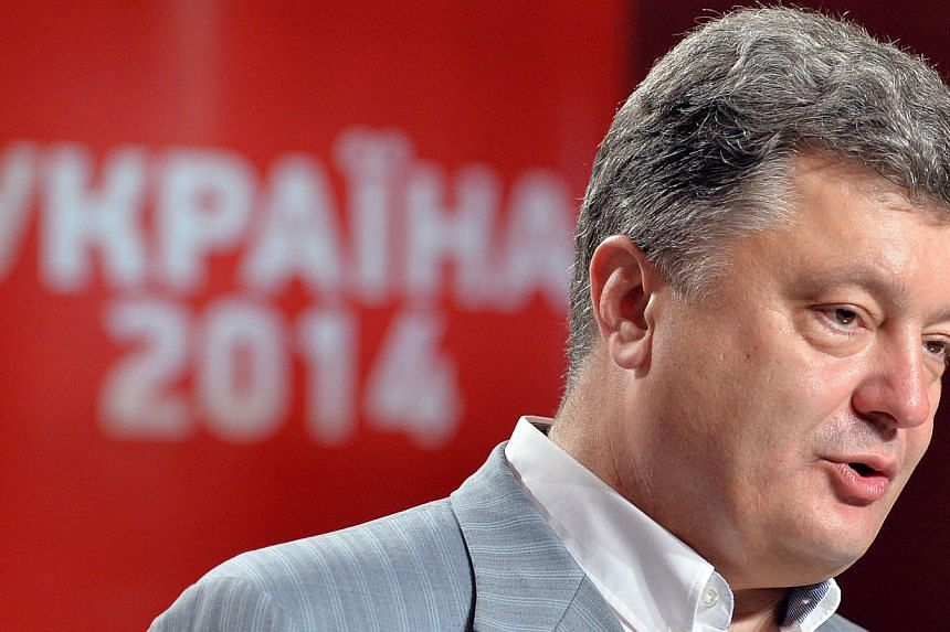 Presidential candidate Petro Poroshenko stands in front of a sign Ukraine-2014 as he speaks during the press-conference in Kiev on May 26, 2014. -- PHOTO: AFP