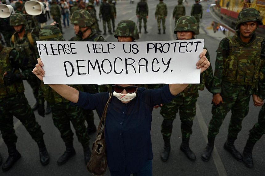 An anti-coup protester holds up a sign in front of soldiers as she takes part in a rally at Victory Monument in Bangkok on Monday. How the international society responds to coups varies greatly.