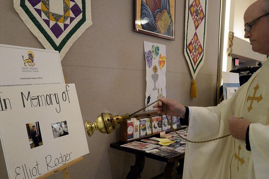 Father John W. Love blesses a placard showing pictures of 22-year-old shooter Elliot Rodger during a service at St. Mark's University Parish in the college town of Isla Vista, California. -- PHOTO: EPA
