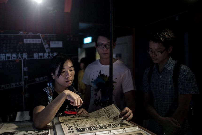 Visitors look at newspaper archives about China's June 4th 1986 Tiananmen military crackdown at the June 4th Museum in Hong Kong on May 28, 2014. Secretary General at Amnesty International Salil Shetty who visited the museum said Hong Kong's deterior
