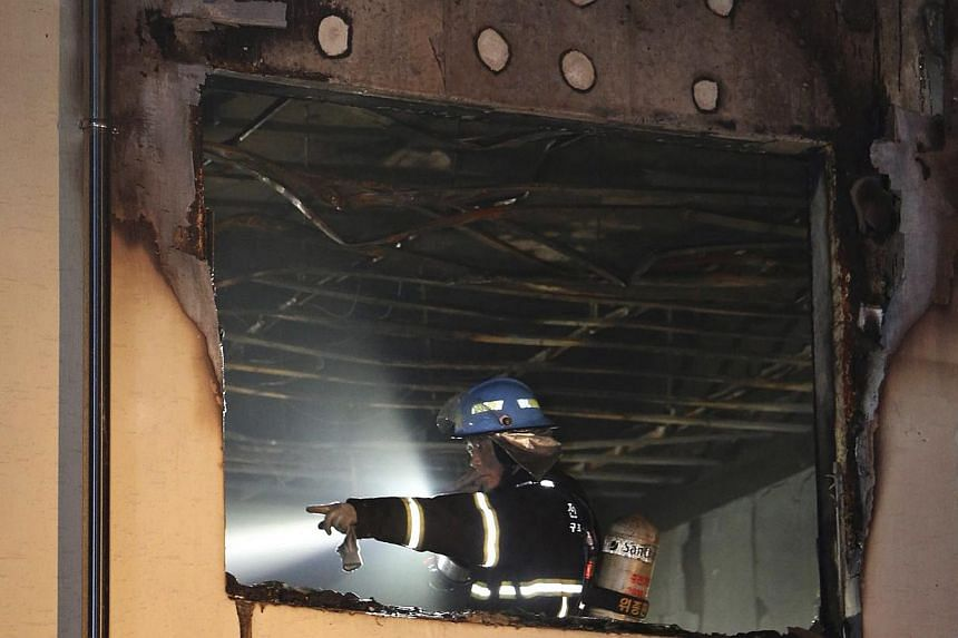 A firefighter works at the scene of a fire at a hospital in Jangseong, south-west region of Jeolla on May 28, 2014. -- PHOTO: REUTERS