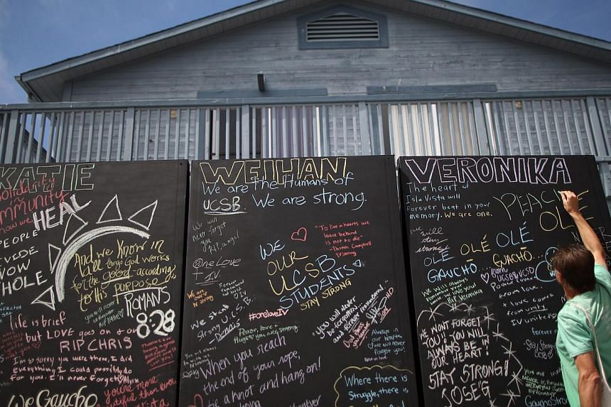 People write chalk messages on a memorial wall for slain students on the Day of Mourning and Reflection for the victims of the Isla Vista, California killing spree. -- PHOTO: AFP