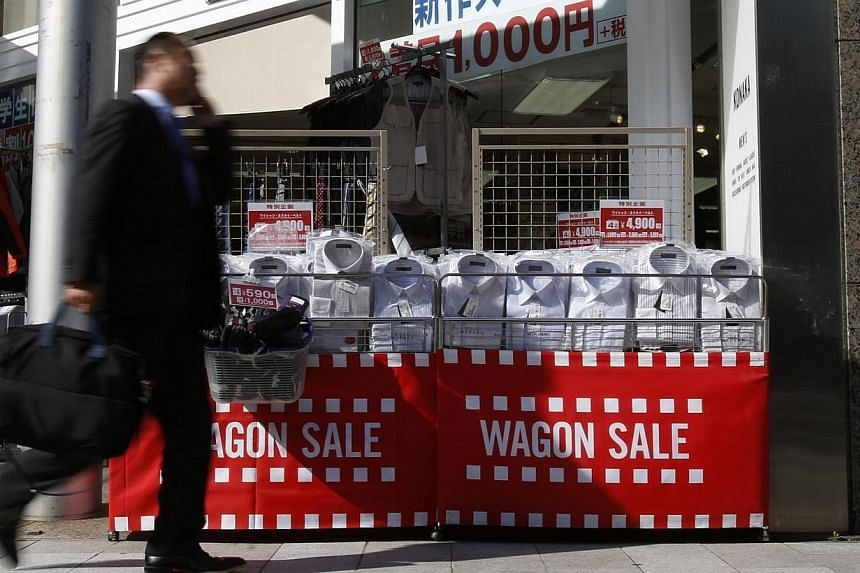 A man walks past shirts on sale outside a store in Tokyo, in this April 7, 2014 file picture. Bank of Japan board member Sayuri Shirai said on Thursday it will take more than two years to achieve the central bank's 2 per cent inflation target, stress
