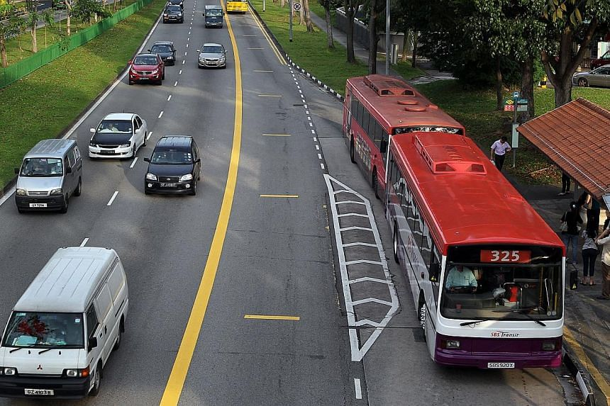 Motorists steering clear of the bus lane at Hougang Avenue 2 during bus lane operating hours. Video cameras are being installed on all new buses to keep check on the road in front.-- PHOTO: ST FILE