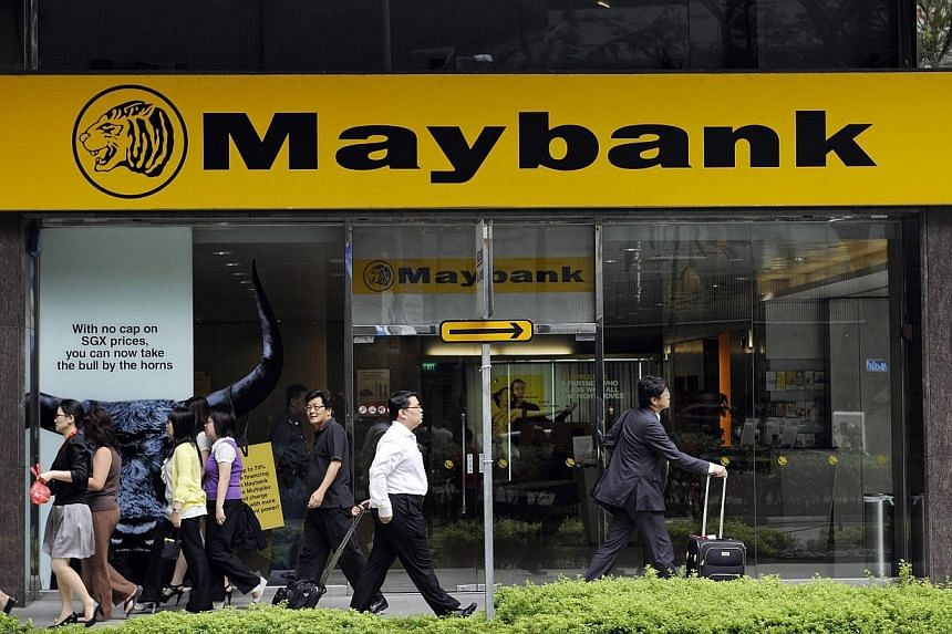 Pedestrians walk past a Maybank branch in Singapore.Maybank Singapore posted strong first quarter results with a 10.5 per cent rise in pre-tax profit to $110.9 million on the back of a 12.2 per cent rise in net income. -- PHOTO: BLOOMBERG