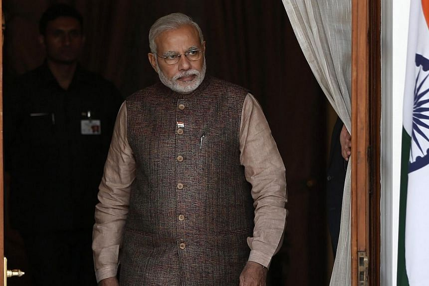 India's Prime Minister Narendra Modi comes out of a meeting room to receive his Bhutanese counterpart Tshering Tobgay before the start of their bilateral meeting in New Delhi on May 27, 2014.India's new Prime Minister Narendra Modi instructed t
