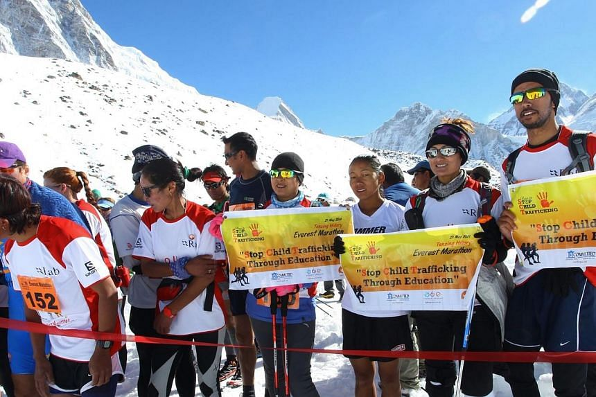 In this photograph received by Himex, the organisers of the Tenzing-Hillary Everest Marathon on May 29, 2014, marathon participants hold banners as they wait at the start of the race at Gorapshep near Mount Everest Base camp in Nepal. -- PHOTO: AFP/H
